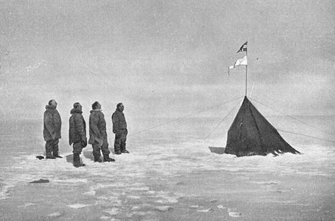 Roald Amundsen and crew facing the Norwegian flag at the South Pole, 1911. Photo via wikipedia.