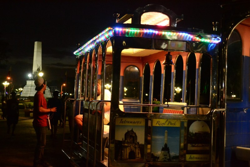 Rizal Park night trolley and tourists.
